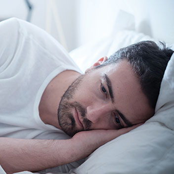 depressed man lying in bed